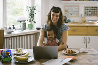 Smiling woman using laptop while sitting with daughter at dining table in house - MASF10800