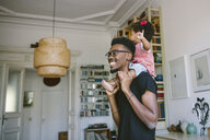 Smiling young man carrying playful daughter at home - MASF10803