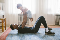 Playful father lifting daughter while lying on carpet at home - MASF10821