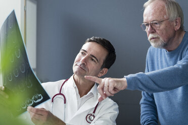 Doctor discussing MRT image with senior patient in medical practice - JOSF02785