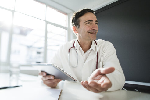 Smiling doctor sitting at desk in medical practice with tablet - JOSF02791