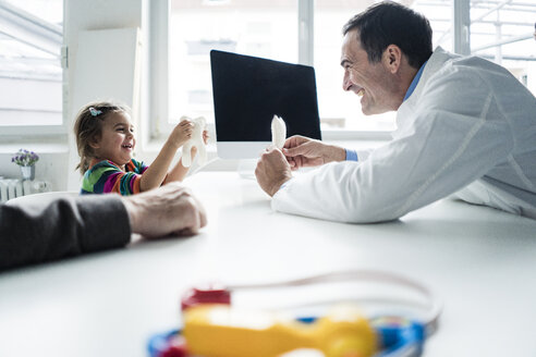 Doctor and happy girl with tooth model at desk in medical practice - JOSF02797