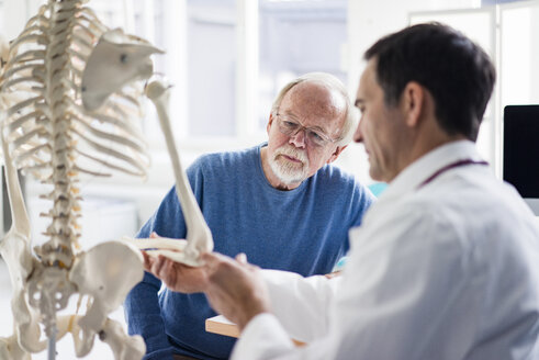 Doctor explaining bones at anatomical model to patient in medical practice - JOSF02809