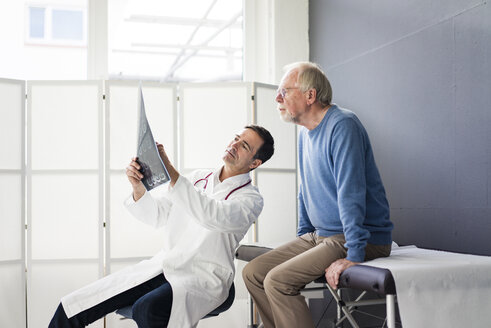 Doctor discussing MRT image with patient in medical practice - JOSF02812