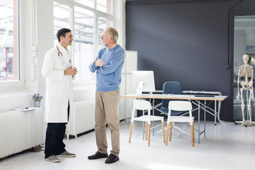 Doctor and patient standing face to face in medical practice - JOSF02824