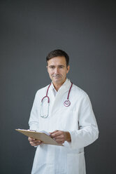 Portrait of confident doctor holding clipboard at a grey wall - JOSF02842