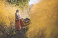 Pregnant woman sitting on chair in asparagus field in autumn - ASCF00918