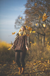 Happy pregnant woman standing on forest path playing with autumn leaves - ASCF00924
