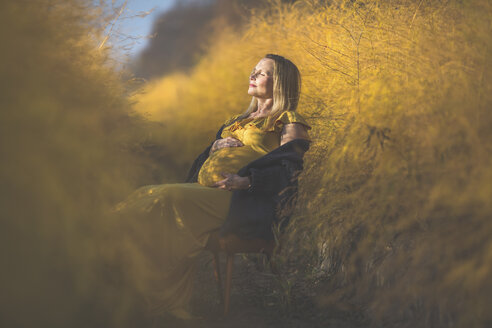 Pregnant woman sitting on chair in asparagus field in autumn - ASCF00930