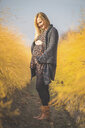 Smiling pregnant woman standing in asparagus field in autumn - ASCF00933