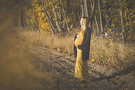 Pregnant woman standing on forest path in autumn - ASCF00939