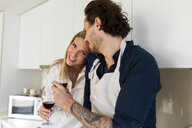 Affectionate couple drinking redwine in the kitchen - VABF02134