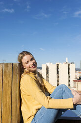 Young woman relaxing on an urban rooftop terrace - VABF02206