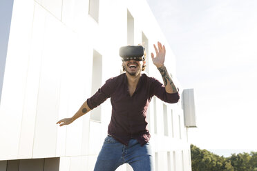 Man on a rooftop terrace, gaming with VR glasses - VABF02215