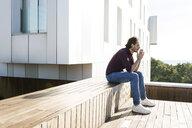 Man sitting on a rooftop terrace, looking worried - VABF02218