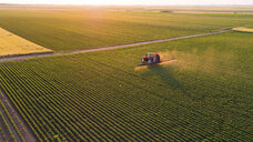 Serbia, Vojvodina, Aerial view of a tractor spraying soybean crops - NOF00075