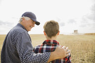 Grandfather and grandson watching combine harvester in field - HEROF04774