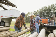 Multi-generation men unloading logs on farm - HEROF04780