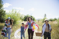 Family walking with beach equipment in rural sunny summer field - HEROF04798