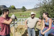 Farmers talking near hay bales on sunny farm - HEROF04828