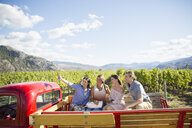 Friends taking selfie with camera phone in truck bed in sunny vineyard - HEROF04855
