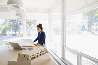 Female architect reviewing blueprints at table in office - HEROF04975