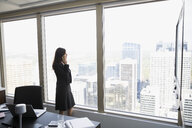 Businesswoman talking on cell phone looking out window at cityscape - HEROF05011