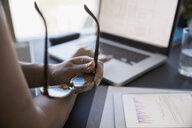 Close up businesswoman holding eyeglasses working at laptop - HEROF05017