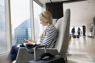 Businesswoman with luggage texting at window in airport lounge - HEROF05056