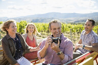 Couples using camera in truck bed in sunny vineyard - HEROF05095