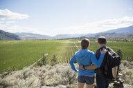 Couple hiking looking at sunny rural vineyard view - HEROF05104