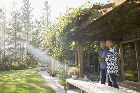 Couple drinking coffee on sunny, idyllic patio - HEROF05110