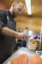 Chef grating lemon over fresh salmon in restaurant commercial kitchen - HEROF05116