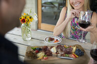Couple enjoying wine and charcuterie at winery patio table - HEROF05128