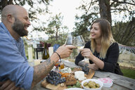 Couple toasting wine glasses at picnic table - HEROF05140