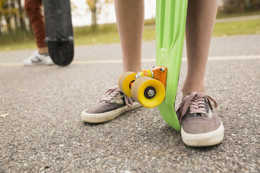 Close up legs of girl with skateboard on path - HEROF05143
