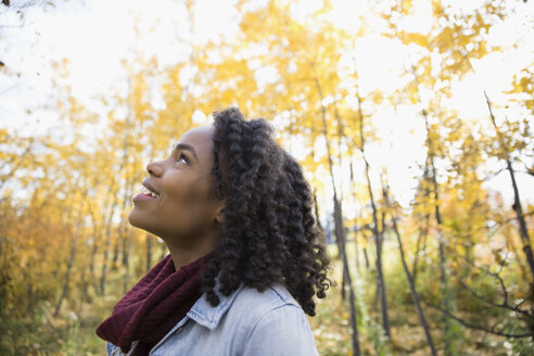Curious woman with curly black hair looking up in autumn woods - HEROF05149
