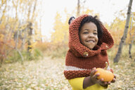 Cute girl holding tiny pumpkin in autumn woods - HEROF05152