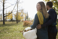 Couple with picnic basket in sunny autumn park - HEROF05155
