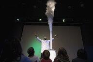Children watching scientist demonstrating geyser cloud in science center theater - HEROF05182