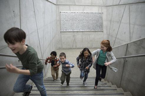 Energetic children running up stairs - HEROF05194
