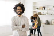 Portrait of a young man with colleagues, working in  a coworking space - AFVF02259