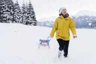 Austria, Tyrol, Thurn, mature woman pulling sledge in snow-covered landscape - PSIF00214