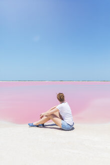 Mexiko, Yucatan, Las Coloradas, Pink Lake salt lake, woman sitting on the beach - MMAF00750