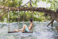 Mexiko, Yucatan, Quintana Roo, lagoon of Bacalar, man sitting on tree swing above the water - MMAF00762