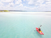 Mexiko, Yucatan, Quintana Roo, Bacalar, woman in kayak on the sea in turquoise water, drone image - MMAF00774