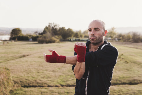 Portrait of boxer stretching outdoors - FBAF00241