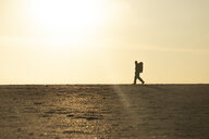 Man with backpack at the beach in the evening light - KBF00404