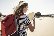Young woman on the beach, carrying surfboard, using smartphone - UUF16433