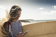 Young woman on the beach, carrying surfboard, using smartphone - UUF16436
